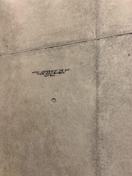 原田左官コンクリート打ち放し風仕上げ壁。カフェの壁面に施工、壁面にはアートやメッセージが書かれている