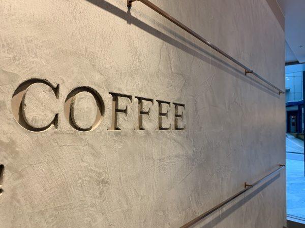 モールテックスで施工されたコーヒーショップの壁面。原田左官施工。壁面上下に金物があり中央に掘り込みのサインがある
