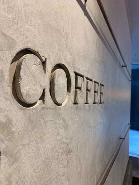 モールテックスで施工されたコーヒーショップの壁面。原田左官施工。掘り込み文字の側面もモールテックス仕上げ