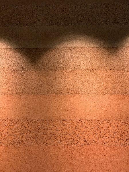 住宅展示場の赤い塗り版築の壁。原田左官施工