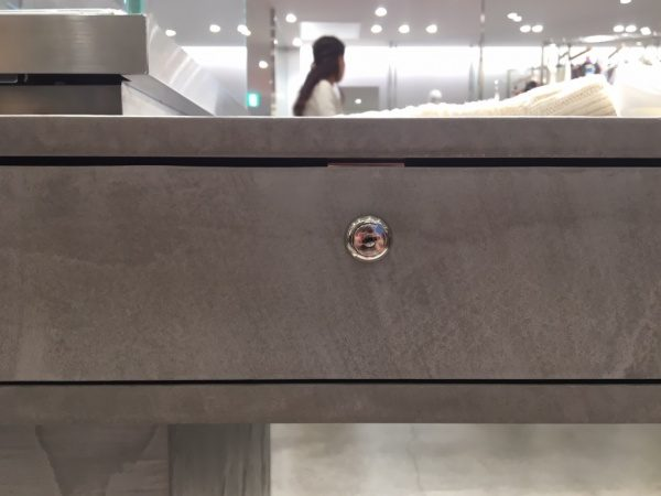 モールテックスグレーのディスプレイテーブル、テーブルの立ち上がり・小口・引き出し部分。原田左官施工