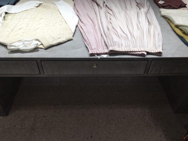 モールテックスグレーのディスプレイテーブルに洋服が置いてある。テーブルは原田左官施工