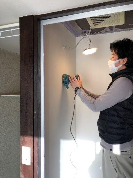 オルトレマテリアメディア白色で塗られたシャワールームの壁を研磨している左官職人さん