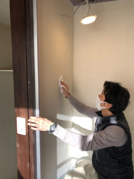 オルトレマテリアメディア白色で塗られたシャワールームの壁を研磨後にクリーニングをしている左官職人さん