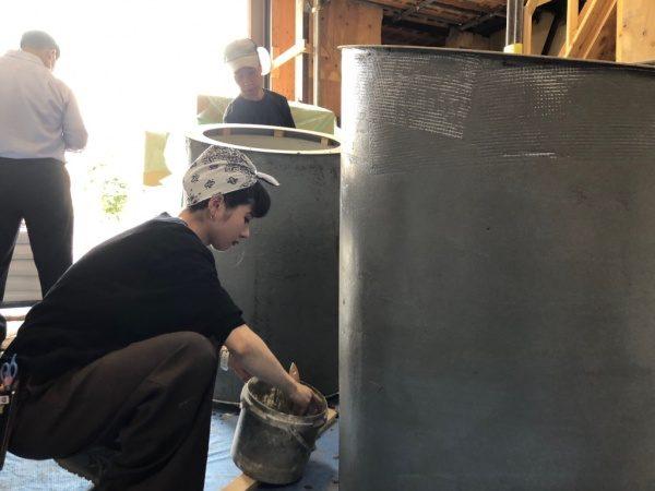 円柱什器にビールストーンの下塗りをする見習工のMさん