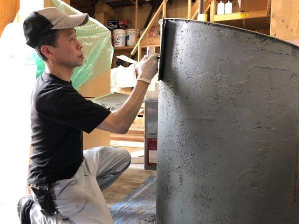 円柱什器にビールストーンの下塗りをする原田左官仕上げ部長の中島さん
