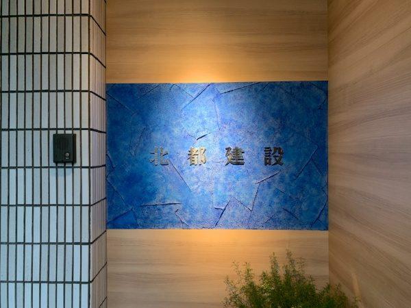 北都建設様エントランス施工完成。樹脂系左官材のブルー、白2色で施工し切り文字が付いた状態