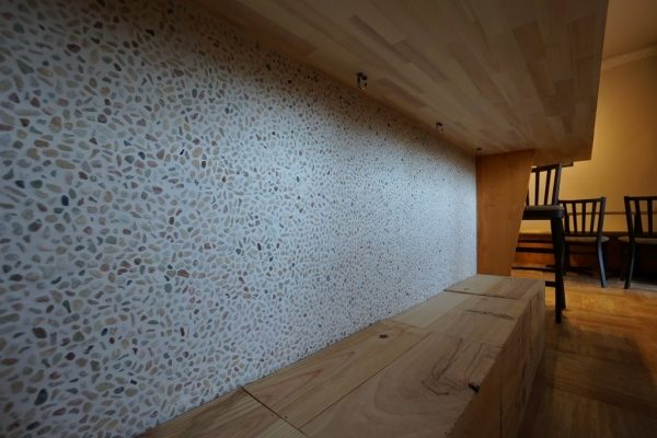 クリスタルイエローの石を使った洗い出しネットストーンの腰壁。原田左官施工