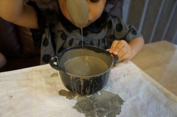 練ったセルフレベリング材キーセルKi-1の硬さを確認している子供