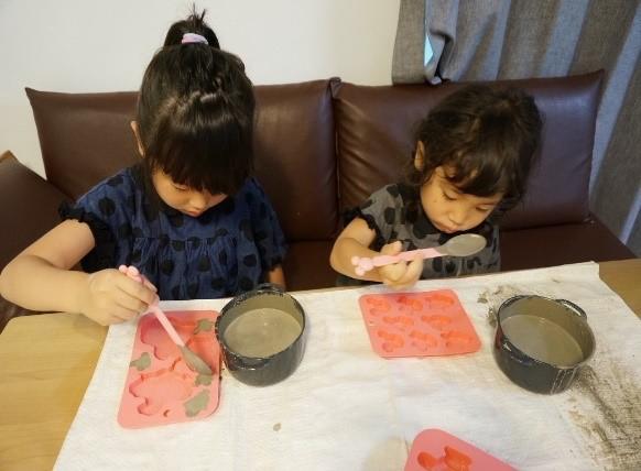 セルフレベリング材キーセルKi-1をシリコンの型にスプーンで流し込んでいる2人の子供