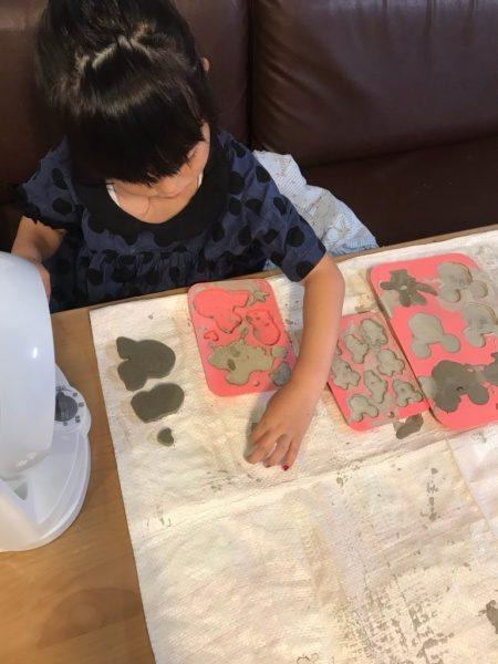 型に流し込んで硬化したセルフレベリング材キーセルKi-1を型から取っている子供。様々な形のものが出来ている