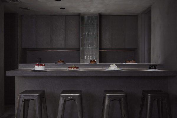 モールテックスのカウンターテーブルと棚や壁。等々力パティスリィアサコイワヤナギの内装、原田左官施工。テーブル上には様々な種類のケーキが並んでいる