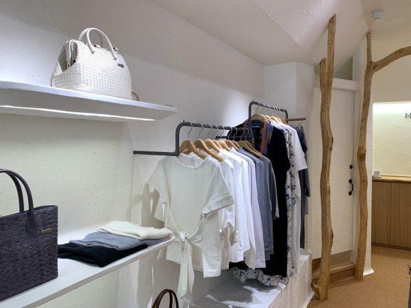 マザーハウス銀座店の内装。原田左官施工の漆喰。店内に服やバッグがある