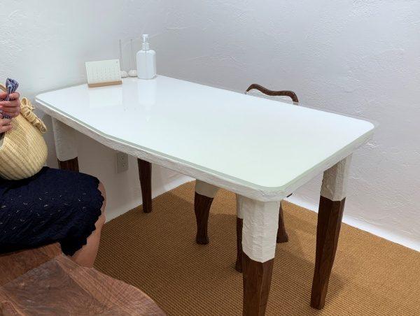 マザーハウス銀座店の内装。原田左官施工の漆喰。ブラックウォールナットのブライダルテーブルや椅子の脚や天板に塗られた漆喰は家具会社さんによる施工