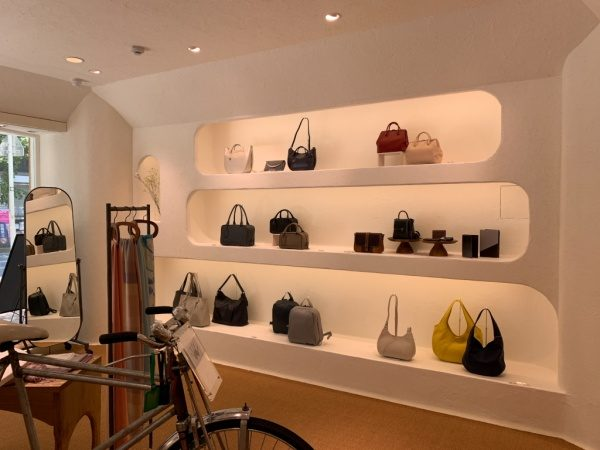 マザーハウス銀座店の内装。原田左官施工の漆喰。店内にバッグがディスプレイされており、自転車も置かれている