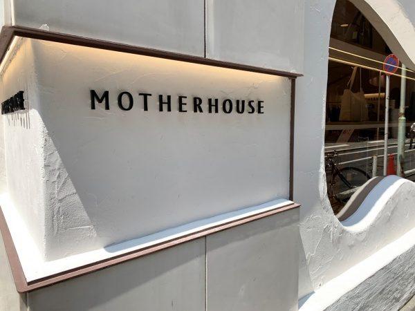 マザーハウス銀座店の外装。原田左官施工の漆喰。店名ロゴがある箇所