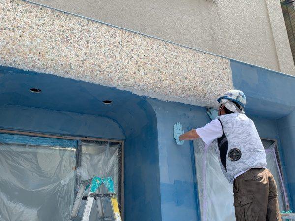 原田左官タイルライブラリーの外壁。外壁にリボール防水施工後に白系統のカラフルな洗い出しネットストーンを施工中の様子