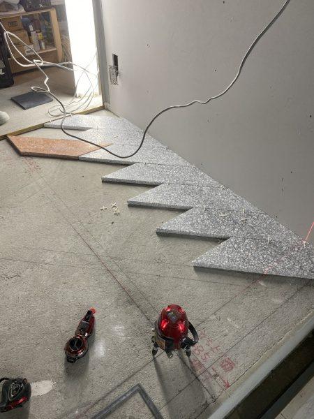 施工前の床に台形にカットされたグレーのテラゾタイルと赤茶のテラゾタイルが並んでいる