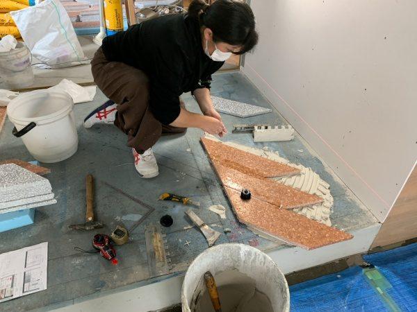 床にレベル(水平)を取りながらデザインテラゾタイルを施工している職人さん