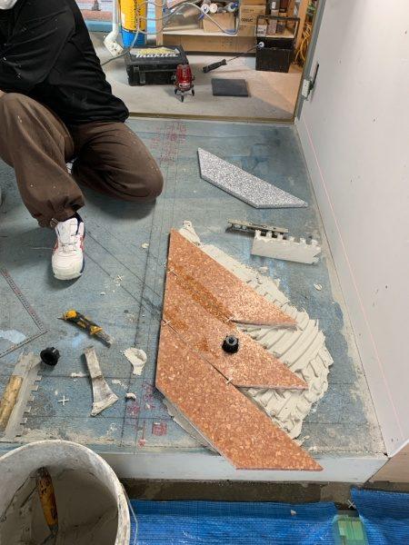 床にデザインテラゾタイルを施工中の様子。赤茶やグレーの台形のタイルを使用