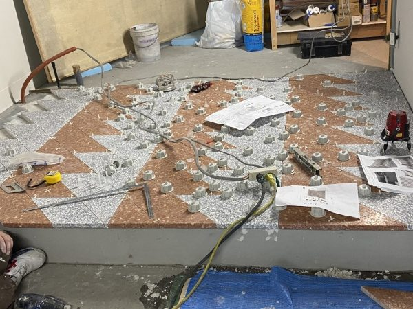 ツイスターレベルという水平器を使って床にデザインテラゾタイルを施工中の様子。赤茶やグレーの台形のタイルを使用