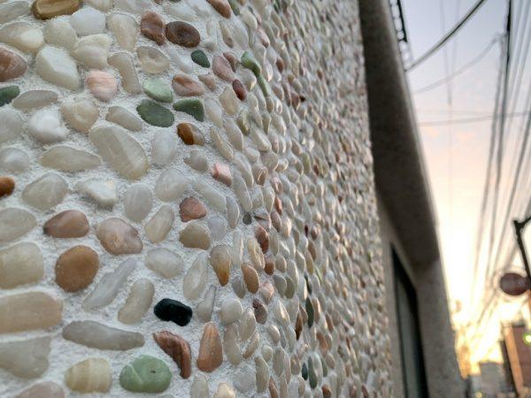 原田左官タイルライブラリーの外壁。洗い出しネットストーンで施工。太陽光で石の艶が見える