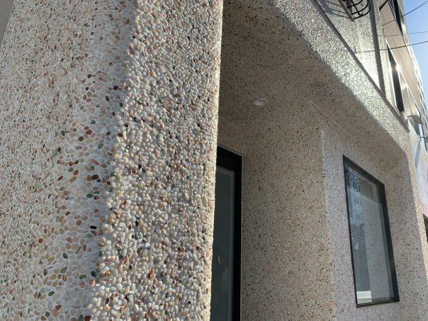 原田左官タイルライブラリーの外壁。洗い出しネットストーンで施工。太陽に照らされてキラッと光っている