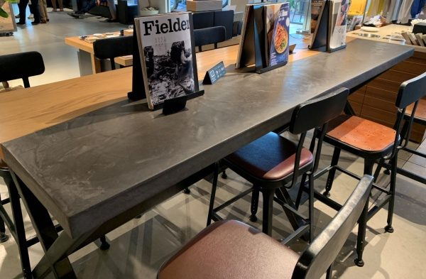 モールテックスグレーのテーブル。カフェのテーブルに原田左官施工。突板とモールテックスで緩やかな曲線のラインに仕上げている