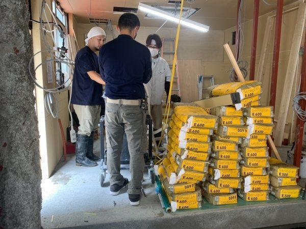 キーセルE600施工前の準備をする原田左官の職人さん達3人。横には材料のキーセルE600の袋が大量にある