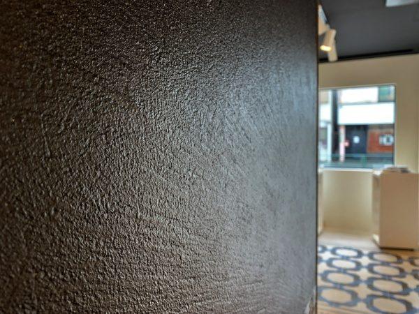 原田左官タイルライブラリー壁。黒いオルトレマテリアの左官パネルで施工