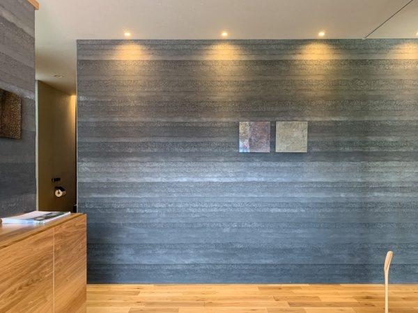 住宅展示場玄関の塗り版築壁。グレー色で層の幅は細め。原田左官施工