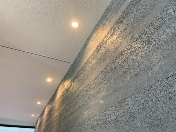 住宅展示場リビングの塗り版築壁。グレー色で層の幅は細め。原田左官施工