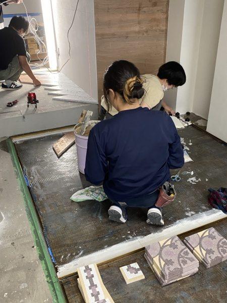 エポキシ工法の下地へテラゾタイルのMIPAを施工中の職人さん達