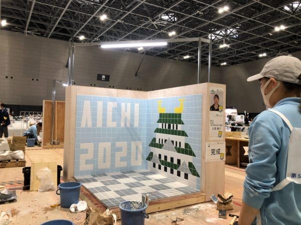 タイル張り競技課題完成した状態の床と壁、壁タイルはAICHI 2020と名古屋城が描かれている。第58回技能五輪全国大会にて。施工が完成した壁と床を眺める職人さん
