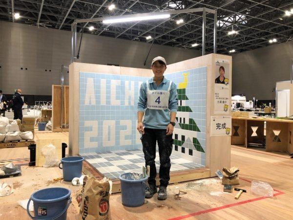 完成したタイル張り競技課題の床と壁の前で笑顔の職人さん。第58回技能五輪全国大会にて