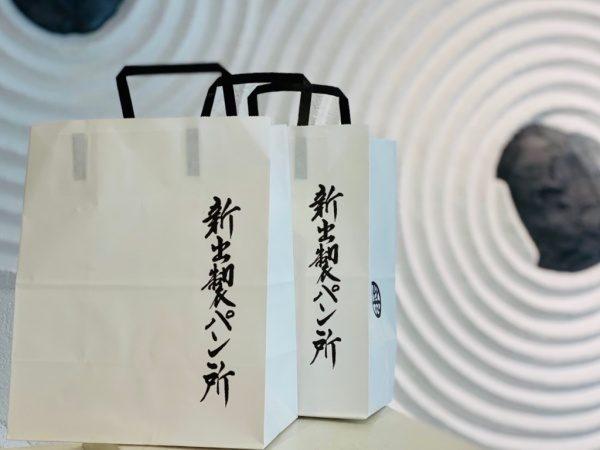 手前に富山新出製パン所様の手提げ紙袋。後ろの壁は枯山水仕上げの壁、原田左官施工
