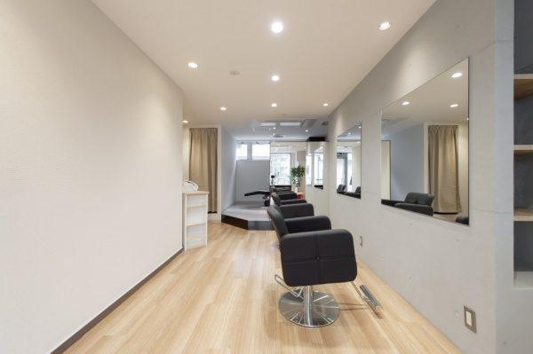 コンクリート打ち放し風仕上げの駒込の美容室エガリテ内壁。原田左官施工。店内には鏡や椅子がある