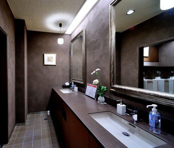 パウダールームの灰炭色の「空KUU」の壁。原田左官施工。洗面台や鏡などがある