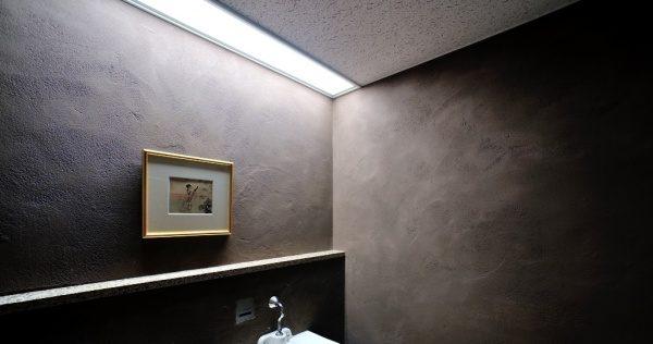 パウダールームの灰炭色の「空KUU」の壁。原田左官施工。壁に絵が飾ってある