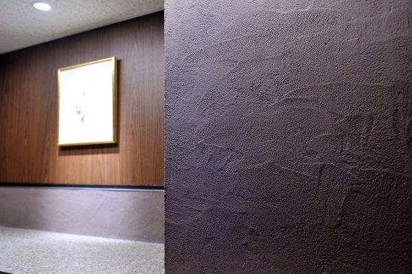 パウダールームの灰炭色の「空KUU」の壁。原田左官施工。壁のアップアングル。奥の板壁に絵が飾ってある