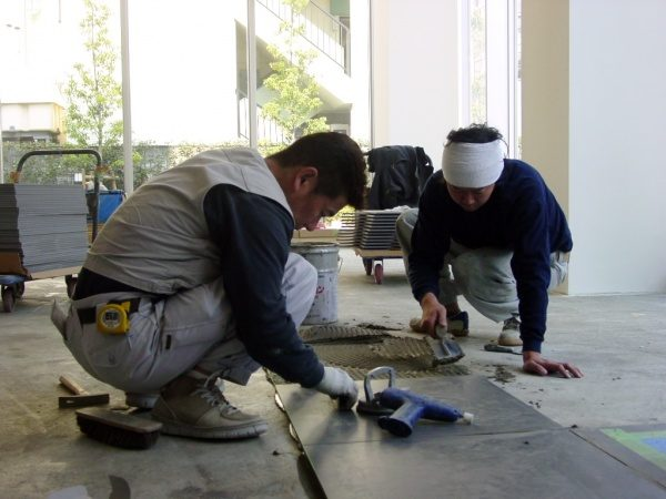 タイル張り作業中のタイル職人さん2名
