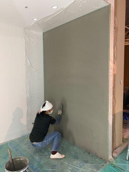 住宅展示場の壁にコンクリート打ち放し風仕上げの下塗り施工中。原田左官施工