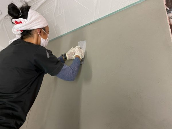 コンクリート打ち放し風仕上げの下塗り施工中の原田左官職人Fさん