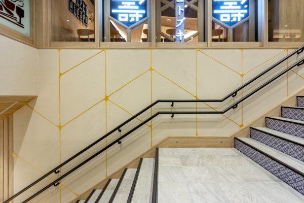 珪藻土仕上げの金継ぎイメージ壁。東京グルメゾンの壁へ原田左官施工。階段踊り場からのアングル