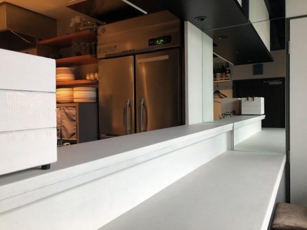 恵比寿のレストランMAENのメインカウンター天板と厨房内壁面。白土の風土仕上げで原田左官施工