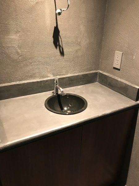 南青山TIME&STLE様の化粧室、特殊モルタル仕上げの壁面と洗面台。原田左官施工