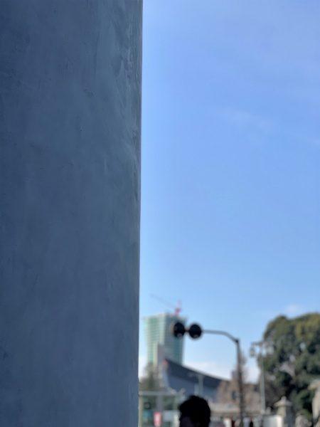 モールテックスグレーで施工のコスメショップ外壁。画像の左側が外壁、右側は空と外の景色