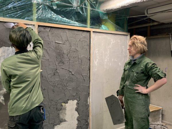 原田左官にて塗り壁トレーニング中のカーリーさん。職人さんが塗る壁を見ている