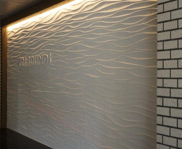 FMサウンドのロゴ入り白色リネアルテ仕上げ壁。原田左官施工