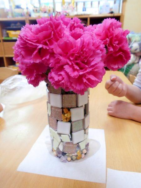 コップにタイルを貼り付けて作られた本駒込こどもヶ丘保育園の卒業制作の作品。コップに花が飾られてある